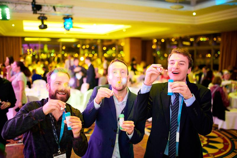 Three alumni blow bubbles at the Alumni Reunion Gala. Image credit: CEU / Daniel Vegel.